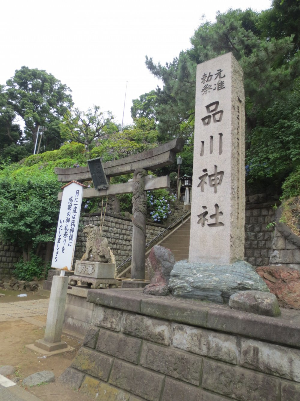 Shinagawa Shrine stone tablet and a sign encouraging people to come once a month