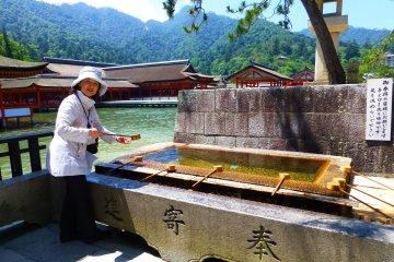<p>โคโทเอะสาธิตวิธีการล้างชำระมือก่อนเข้าศาลเจ้าอิตสุคุชิมะ</p>