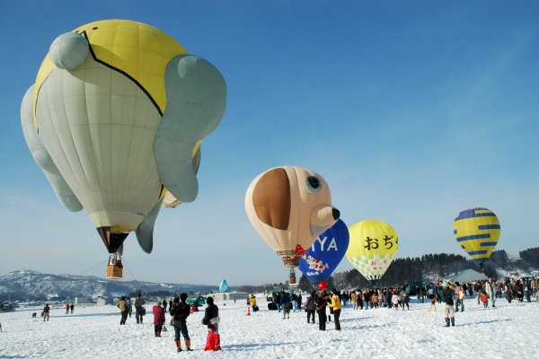 The snowy white landscape is filled with brightly colored balloons
