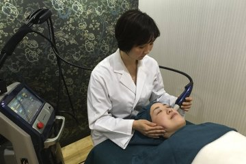 Dr. Naoko Hitosugi administering a skin treatment on a patient