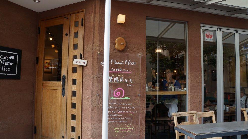 """Một chiếc đồng hồ hình hạt đậu nhỏ treo ở cửa (""""mame"""" trong tên của quán cà phê có nghĩa là """"đậu"""" trong tiếng Nhật)"""