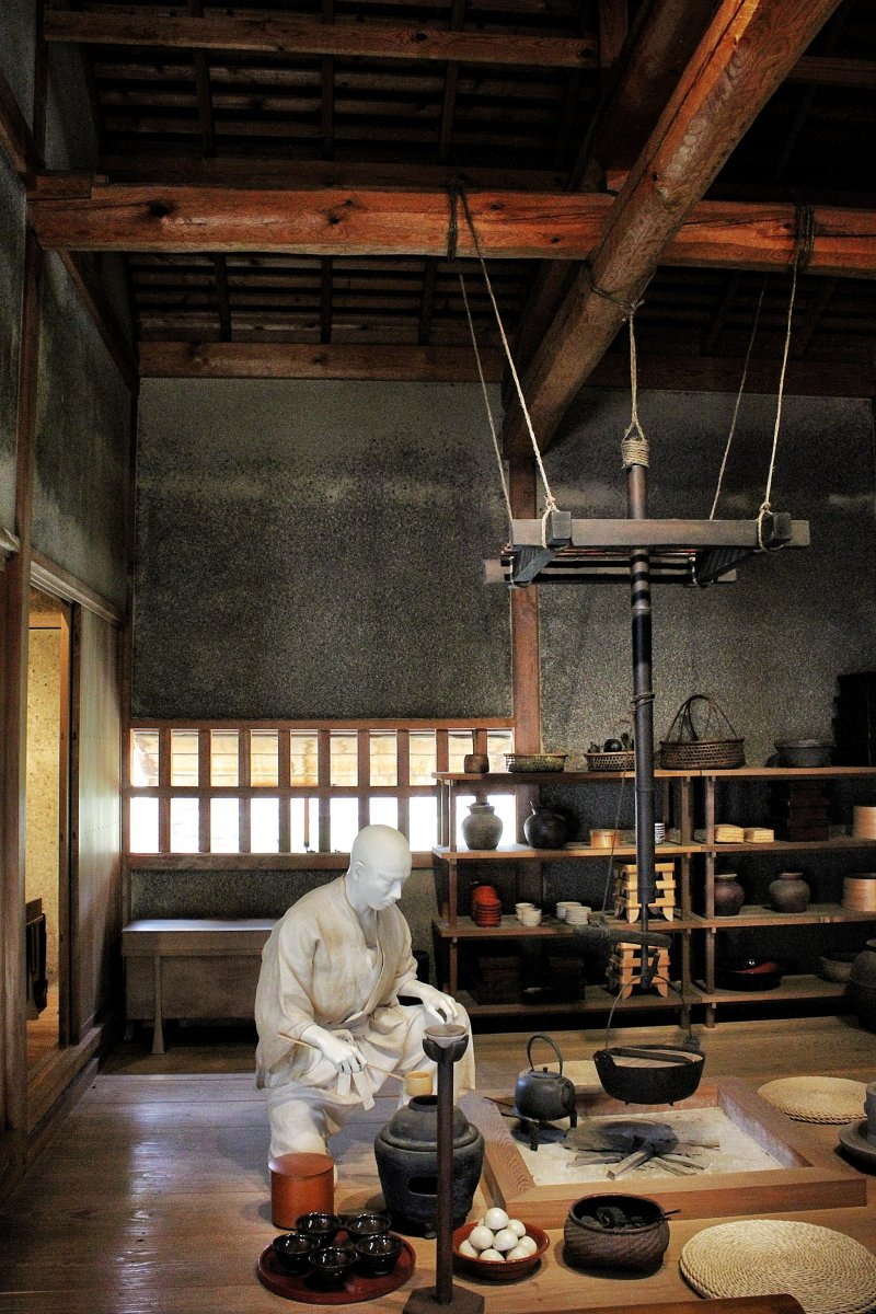A servant prepares food in the grounds of Yuzuki Castle