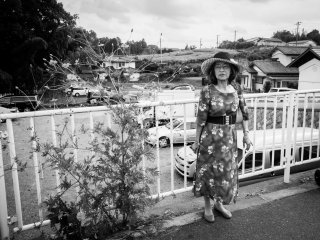 Here's a B&W photo of a somber Japanese lady waiting for her travel group on the side of a bridge at red spider lily festival in Saitama.
