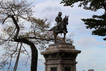 Памятник обращён лицом к городу, лежащему у подножия горы Аоба