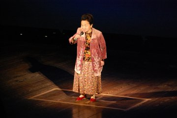 An Uchiko local performs a karaoke number at a town event.