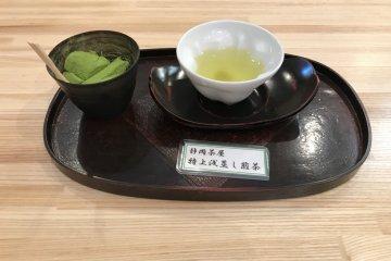 Samples of green tea and warabi mochi dusted in matcha powder