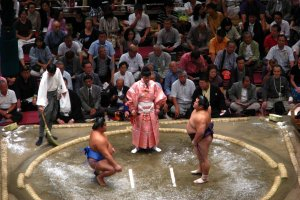 A pair of rikishi wrestlers and the gyoji referee between them.