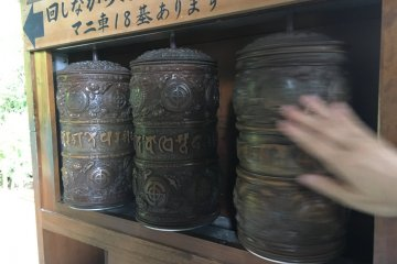 These are called 'mani-guruma'. Sutras are kept inside. Turning them is equivalent to reading a verse