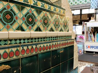 The wall is covered with colourful Majolica tiling
