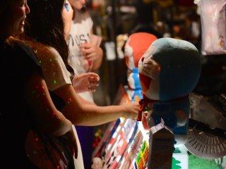 สาววัยรุ่นกำลังวุ่นอยู่กับการเลือกซื้อตุ๊กตา