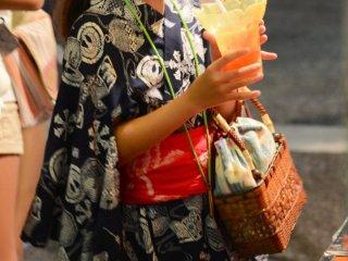 สาวน้อยในชุดกิโมโนกำลังดื่มน้ำแข็งปั่น