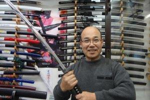山海堂のオーナー、亀ケ谷さん。かっこ良く刀を構えてポーズ