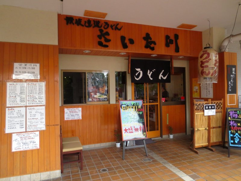 The entrance with many colorful advertisements and promotions offsetting the traditional wooden look