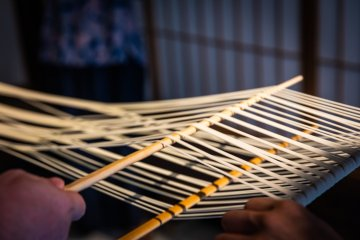 The traditional way: udon noodles are separated with wooden sticks before hanging to dry