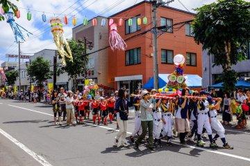 เด็ก ๆ เดินขบวนไปบนถนนพร้อมกับแบกเสลี่ยงดาชิ