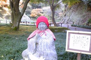 """I was walking through this pretty garden looking at autumn leaves then I found a little """"Jizo Red""""(赤地蔵). Dressed in red, Jizo is a small statue—just like a guardian angel—and it had a poem attached."""