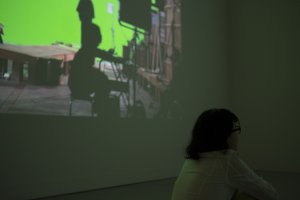 A woman watches the main film while the making of is projected just to her left