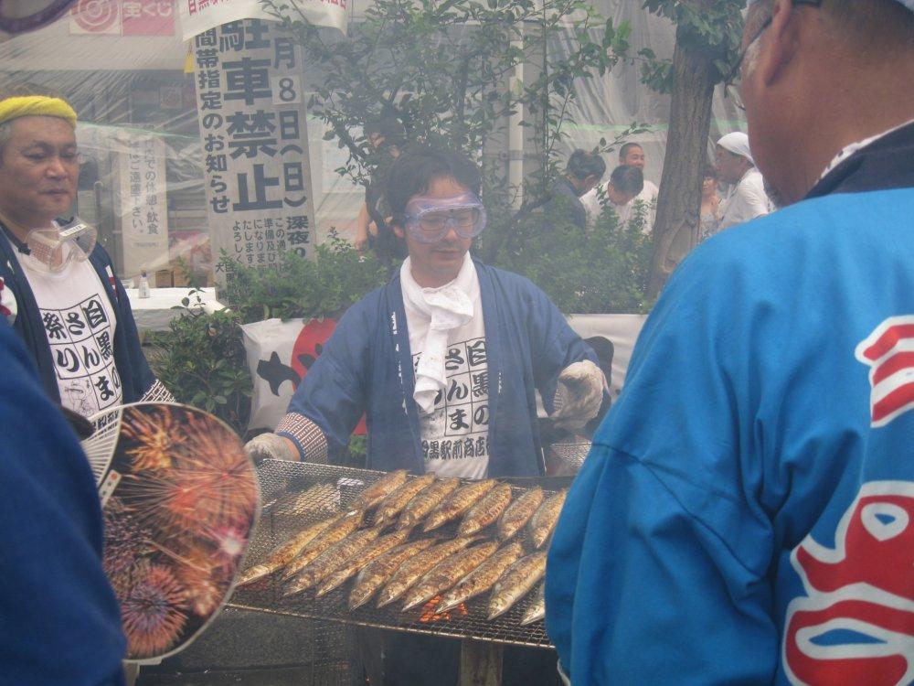 """说起日本的""""祭""""大家应该不陌生。今天就向大家展示一个 日本的秋季""""祭""""。在目黑站前举行的""""秋刀鱼祭""""。大家可以免费品尝秋刀鱼,然后自己自愿捐款来支援灾区。此图就是大家烤秋刀鱼的景象。"""
