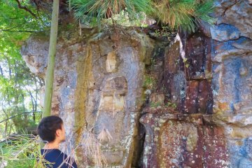Studying the carvings at Iwaya Kannon