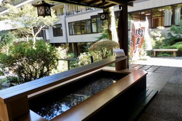 Visitors can soak their feet in an onsen foot bath while enjoying a drink in the garden.