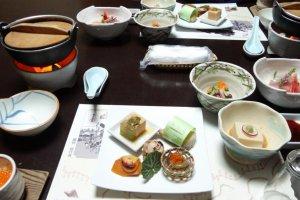 """Depois de apreciar o esplêndido pôr-do-sol a partir da janela, a nossa """"cuidadora"""" - uma senhora chamada Mari - trouxe-nos o jantar ao quarto. Incluía uma grande variedade de marisco local de Enoshima."""