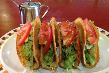 Okinawan tacos are prepared with rice-based taco shells, flavorable chili spiced beef, cheese, shreeded lettuce and tomatoes, and are made exactly the same each time; taco sauce is served in a coffee creamer pitcher with a spoon