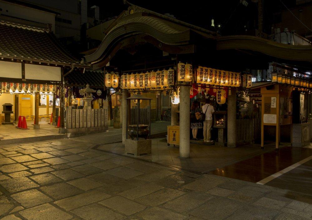 The lanterns of the shrine illuminate the cobblestones at night at Hozenji Yokocho between Nanba and Dotonbori