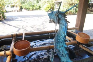 The beautiful blue-green dragon on the purification trough. The ladle is used to rinse both hands as well as mouth in the purification ritual.