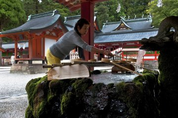 You should take one of the ladles provided, fill it with fresh water and rinse both hands. Then transfer some water into your cupped hand, rinse your mouth and spit the water beside the fountain.