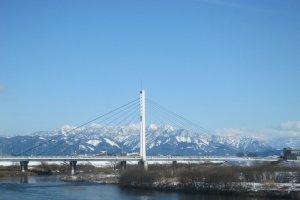 冬の中角橋。遠くに雪をかぶった奥越の山並み
