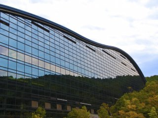 A massive glass building was embedded into the forest, and the reflection of the forest on that building was as clear as mirror's image.