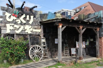 <p>Bikkuri Donkey&#39;s Chatan location is decorated with faded wood and old aluminum siding</p>