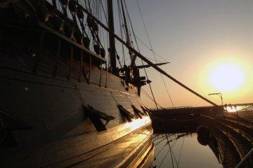 <p>Los ca&ntilde;ones del barco descansan tranquilamente en sus escotillas al atardecer.</p>