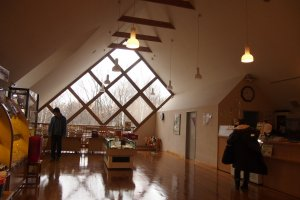 The Cheese Factory is housed in a large barn house with large transparent windows.