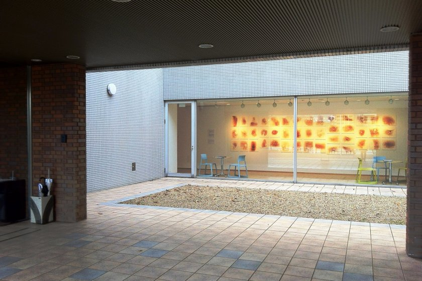 The courtyard at the ARTCOURTgallery with Yo Akiyama's spiderweb prints visible through the glass
