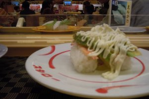 I am a big fan of avocado with sushi. I got hooked in Canada, where the combination is common. I think this is peeled cooked prawn topped with avocado sauce and mayonnaise. My other favorites were devoured too quickly for me to remember to take a photo; if you like nuts, try the sushi topped with nuts