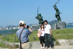 A couple is taking a picture in front of the statues