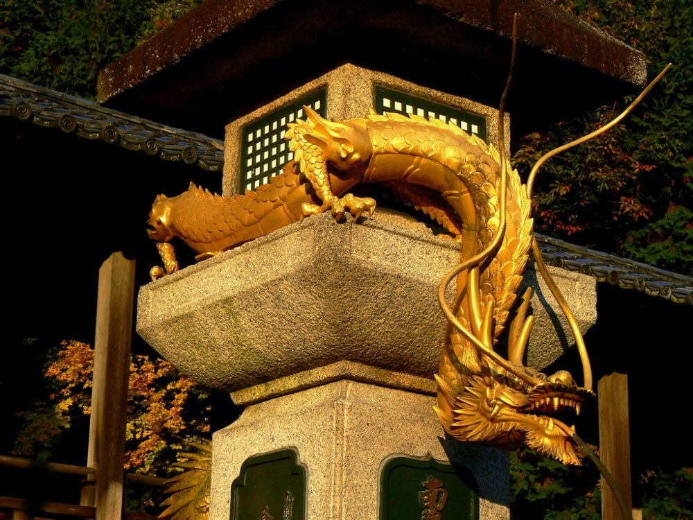 An impressive golden dragon coils around a large stone lantern. Water spouts from his mouth into a basin below. I was told that if you wash money in the water, it will increase
