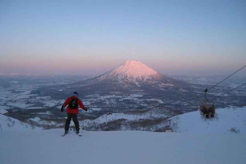 Un skieur descend une piste avec le mont Yōtei en arrière-plan