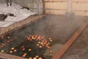 บ่อน้ำพุร้อนในตอนเย็นที่มีแอปเปิ้ลที่ลอยอยู่ในน้ำที่ให้ออกกลิ่นหอมที่สวยงาม