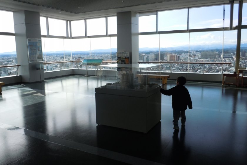 My son pausing at the showcase of a scale model of the building, on his way to the windows no doubt