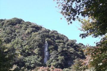 <p>There&#39;s a rock in the hill with large kanji characters carved into its face</p>