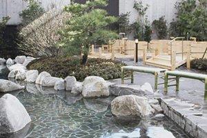 บ่อน้ำพุร้อนด้านนอกที่ล้อมรอบด้วยสวนแบบญี่ปุ่น