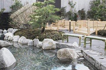 <p>บ่อน้ำพุร้อนด้านนอกที่ล้อมรอบด้วยสวนแบบญี่ปุ่น</p>